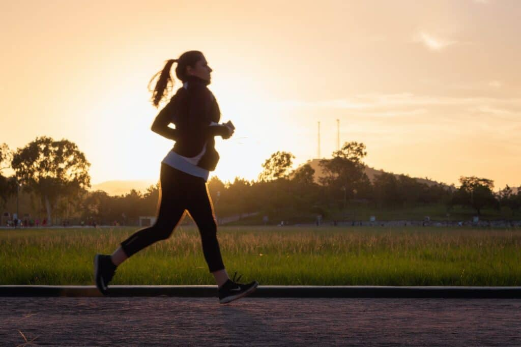 woman in black sports bra and black pants running on water during sunset