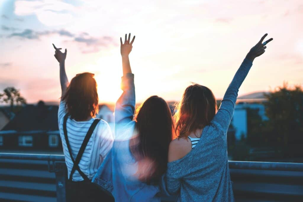 photo of three women lifting there hands